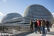 People walk past Soho Galaxy, a Zaha Hadid designed mix-use complex in Beijing, China, on Tuesday, Dec. 01, 2015.