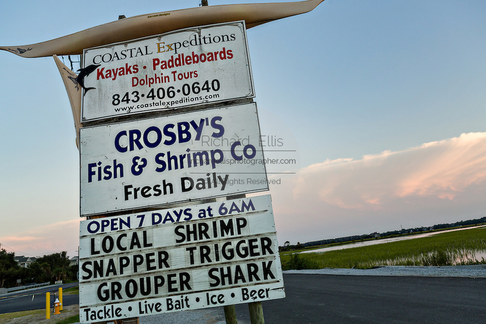 Sign advertising Crosby Fish & Shrimp shop at sunset in Folly Beach, SC.