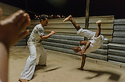 Baiano, in the right, whose name is Alessandro, performs a Beija Flor, a Capoeira movement. Baiano is a self-taught designer and Master of Capoeira, an afro-brazilian martial art that joins dance and fight. He coordinates a social project in Esperança Occupancy, Isidoro area, whose objective is integrates all community through sports. As a low-income initiative, all structure, musical instruments and uniforms are donated or achieved by community effort.