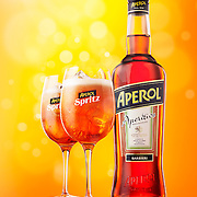 Beauty bottle and two Aperol filled glasses with ice Ray Massey is an established, award winning, UK professional  photographer, shooting creative advertising and editorial images from his stunning studio in a converted church in Camden Town, London NW1. Ray Massey specialises in drinks and liquids, still life and hands, product, gymnastics, special effects (sfx) and location photography. He is particularly known for dynamic high speed action shots of pours, bubbles, splashes and explosions in beers, champagnes, sodas, cocktails and beverages of all descriptions, as well as perfumes, paint, ink, water – even ice! Ray Massey works throughout the world with advertising agencies, designers, design groups, PR companies and directly with clients. He regularly manages the entire creative process, including post-production composition, manipulation and retouching, working with his team of retouchers to produce final images ready for publication.