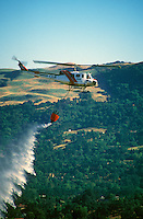 A helicopter dumping water on a forest fire.