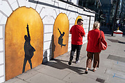 Both wearing red, two Londoners walk past a billboard outside the Victoria Palace Theatre where the hut musical Hamilton is currently playing, on 24th September 2021, in London, England.
