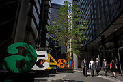 City workers pass-by an art installation entitled 'One Through Zero (The Ten Numbers)' by American pop artist Robert Indiana (b 1928), in Lime Street, City of London, the capital's Square Mile, and its financial heart. Situated in the capital's Square Mile, its financial heart, are surrounding offices and corporate headquarters from the finance and insurance sector, most notably being the nearby Lloyds of London building. This series of sculptures is composed of 10 brightly painted numerical digits, each made of aluminum and set on its own base. Their construction took place at the former Lippincott Foundry in North Haven, Connecticut from 1980 to 1983