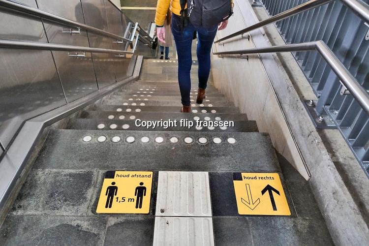 Nederland, Nijmegen, 12-5-2020  Centraal station vanaf 1 juni is het verplicht een mondkapje te dragen in het openbaar vervoer. In de stationshal en op het perron bij de poortjes en trappen zijn stickers aangebracht met pictogrammen om anderhalve meter afstand te houden tot elkaar .Foto: Flip Franssen