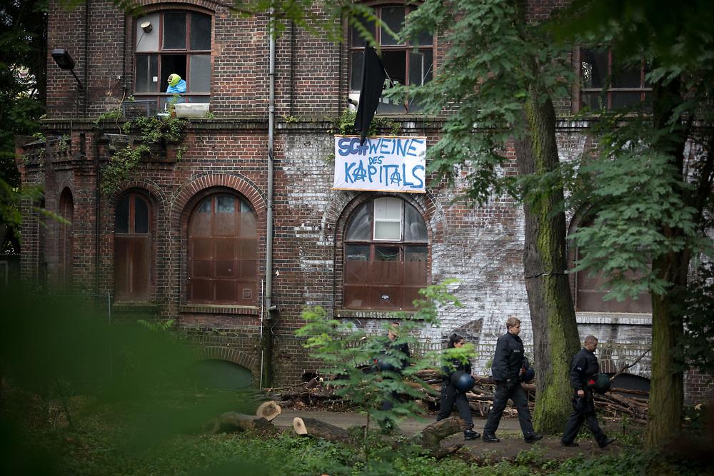An die 100 Menschen protestieren vor der besetzen ehemaligen Teppichfabrik auf der Halbinsel Stralau in Berlin Friedrichshain gegen eine Räumung des Gebäudes. Der Eigentümer des seit einigen Monaten besetzten Industriegeländes hat vor dem Berliner Landgericht einen Räumungstitel erwirkt, der jederzeit umgesetzt werden kann. Hausbesetzer an den Fenstern des besetzen Gebäudes mit Banner: Schweine des Kapitals.<br />  <br /> [© Christian Mang - Veroeffentlichung nur gg. Honorar (zzgl. MwSt.), Urhebervermerk und Beleg. Nur für redaktionelle Nutzung - Publication only with licence fee payment, copyright notice and voucher copy. For editorial use only - No model release. No property release. Kontakt: mail@christianmang.com.]
