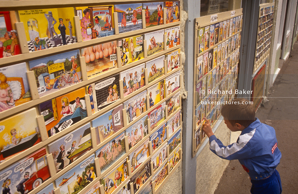 A young boy looks carefully at the many saucy postcards on sale outside a seaside shop, on 19th July 1993, in Scarborough, North Yorkshire, England. Telling jokes to send back to friends and family, they using cartoon characters of buxom women, hen-pecked husbands or sexually-frustrated young men, the humour is bawdy and cheeky - the epitome of seaside holiday kitsch. The best-known saucy seaside postcards were created by Bamforths (founded 1870) and despite the decline in popularity of postcards that are overtly tacky, postcards continue to be a significant economic and cultural aspect of British seaside tourism. In the 1950s, Bamforth postcards were among the most popular of the 18 million items purchased at British resorts.