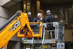 © Licensed to London News Pictures. 15/10/2019. London, UK. XR activist and co-founder Gail Bradbrook climbs on top of the entrance of the Department Transport and hammers the glass as police arrest her with a JCB. Activists continue to occupy roads around Westminster and the City for the 9th day. Photo credit: Alex Lentati/LNP