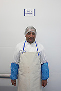Portrait of an employee in apron  of fish product importers New England Seafoods, standing in the processing room