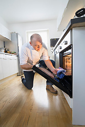 Chef removing tray from oven in private kitchen