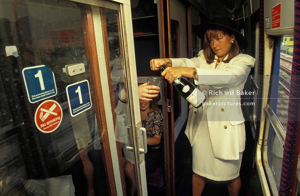 Girlfriends eagerly await the opening by one woman of a bottle of bubbly, en-route by First Class train carriage to Ascot racecourse on Ladies Day at Royal Ascot racing week, on 21st June 1993, in London, England. Royal Ascot is held every June and is one of the main dates on the sporting calendar and English social season. Over 300,000 people make the annual visit to Berkshire during Royal Ascot week, making this Europe's best-attended race meeting.