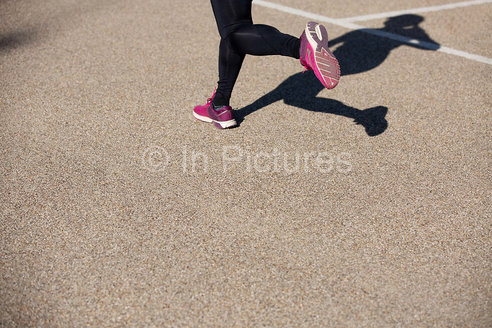 A female runner wearing black leggings and pink running trainers taking part in a 10 kilometre running event at the Queen Elizabeth Olympic Park on the 21st September 2019 in London in the United Kingdom. RunThrough is a London based running community who organise regular running events, training sessions as well as coaching.
