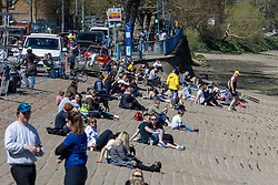 Licensed to London News Pictures. 18/04/2021. London, UK. Members of the public enjoy the sunshine along the Thames in Putney, South West London on the first weekend of the easing of Covid-19 restrictions. Shops, pubs, bars and restaurants are now serving customers for the first time in over 4 months as a mini heatwave is set to hit the UK this week with temperatures predicted to reach up to 18c in London and the South East. Photo credit: Alex Lentati/LNP