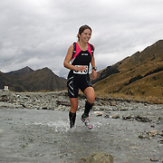 Runner Isobel Barry crosses Moke Creek on the Ben Lomond High Country Station during the Pure South Shotover Moonlight Mountain Marathon and trail runs. Moke Lake, Queenstown, New Zealand. 4th February 2012. Photo Tim Clayton