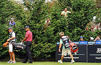 Residents in their own backyards get a vantage point through trees to watch Tiger Woods arrive at the 17th tee at Kingston Heath Golf Course for the 2010 Australian Masters. (Copyright Michael Dodge/Herald Sun)