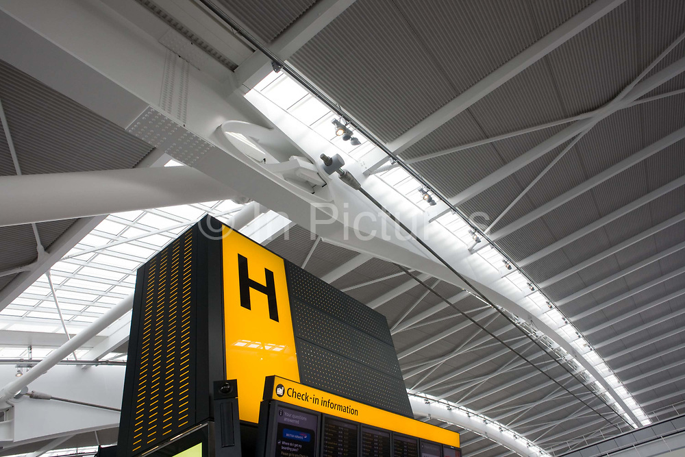 """Seen from ground level, we see one of the giant 'hand nodes' of Heathrow Airport's Terminal 5 roof structure. Developed by Arup to design the geometry of abutment steel supports, this engineering challenge needed to help support 50 ton tusk rafters to made T5 the largest free-standing building in the UK. A large H denotes the check-in zone for international passengers. The main architecture was created by the Richard Rogers Partnership (now Rogers Stirk Harbour and Partners) and opened in 2008 after a cost of £4.3 billion. Terminal 5 has the capacity to serve around 30 million passengers a year. From writer Alain de Botton's book project """"A Week at the Airport: A Heathrow Diary"""" (2009)."""