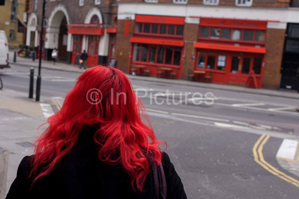 Seen from the rear, an anonymous red-haired woman walks towards a business using red as its theme of frontage in north London. Dyed as bright as a prime colour to make her own personal fashion and style statement, she has made a choice to show her individuality and uniqueness.