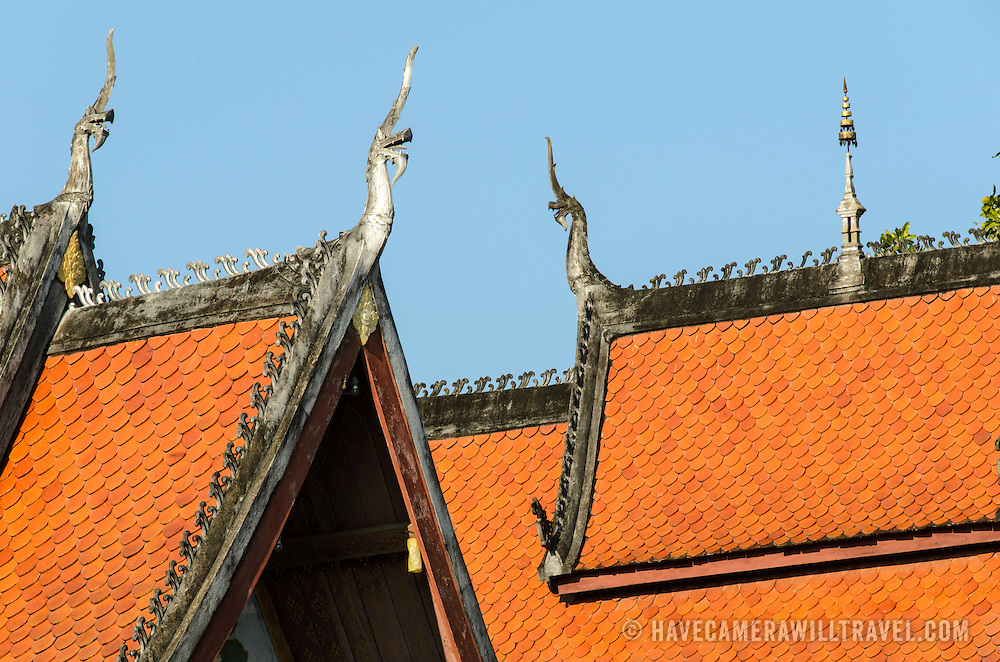 The orange tiles of the multi-tiered roof of Wat Sensoukharam in Luang Prabang, Laos. The roof's points are decorated with chofah, depictions of Garuda, the half-man, half-bird that the Hindu god Vishnu ride.