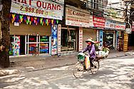Street vendor cycles through a quiet street of Hanoi, Vietnam, Southeast Asia