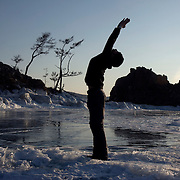 Justin exercises on the coast of Olkhon Island on Lake Baikal in Siberia, Russia. .They are a group of five people: Justin Jin (Chinese-British), Heleen van Geest (Dutch), Nastya and Misha Martynov (Russian) and their Russian guide Arkady. .They pulled their sledges 80 km across the world's deepest lake, taking a break on Olkhon, the world's forth-largest lake-bound island. They slept two nights on the ice in -15c. .Baikal, the world's largest lake by volume, contains one-fifth of the earth's fresh water and plunges to a depth of 1,637 metres..The lake is frozen from November to April, allowing people to cross by cars and lorries.