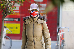 © Licensed to London News Pictures. 22/04/2020. London, UK. A woman wearing a 'Union Jack' design face mask in north London during the coronavirus lockdown. Members of the public will be asked to wear face masks in public to stop the spread of COVID-19. Photo credit: Dinendra Haria/LNP