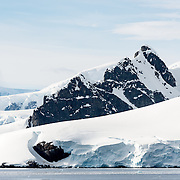 Mountains rise up dramatically from the shore of the Gerlache Strait on the Antarcic Peninsula.