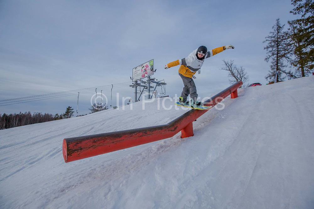 A snowboarder in the snowpark at Zagarkalns ski resort on the 14th February 2019 in Zagarkalns in Latvia. Zagarkalns is a small ski resort in the north eastern region of Latvia. It is close to the historic town of Cesis.
