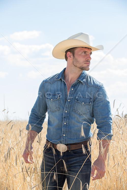 hot rugged cowboy in a beautiful field