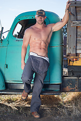 hot man with overalls and no shirt by a vintage truck