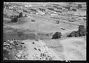 """ackroyd_00870-6. """"Guilds Lake aerials. For Union Pacific. August 6, 1948."""" The vacant land in the center is the subject of this photo, it is the land on the south side of NW Yeon Ave. at the intersection of NW 26th Ave., which is address numbered in the 3200s. The intersection in the center is NW Yeon & NW 26th Ave. In the foreground is the Calbag junkyard, where two men are burning a slash pile of junk (appears to be electric wire). The largest building in the center is Industrial Air Products owned by Gilbert Schnitzer 3200 NW Yeon. To its right is Dulien Steel 3190 NW Yeon"""