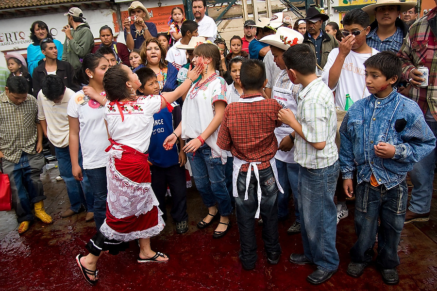 A girl covers her friend's face with blood at the ritual killing of a bull in Paracho, Michoacan state, Mexico on August 8, 2008 during the annual Feria Internacional de la Guitarra. The bull was slaughtered and used to stock the town's meat locker while butchers served beef stew to the public to conclude the parade held by the town's market vendors.