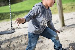 Boy playing swing playground sand action