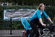 A woman cyclist passes a pollution awareness banner that is attached to the railings of Dulwich Hamlet School, where restrictions also prevent traffic from passing through at morning and afternoon rush-hour times in the borough of Southwark, on 14th June 2021, in London, England.