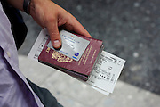 """A close-up detail of a male passenger's hand that holds on to his family's travel documents before proceeding to his British Airways check-in zone at Heathrow Airport's Terminal 5. With a Silver company Executive 'One World' loyalty card, his ticket and British passport to hand, he waits in line after registering at a self-service kiosk where his seat has been designated. A BA employee then only needs to take his luggage. From writer Alain de Botton's book project """"A Week at the Airport: A Heathrow Diary"""" (2009)"""
