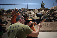Mr. Marc Sarosi watch his son practicing with a paint ball gun.
