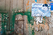 """Tripoli, Lebanon - September 7, 2010: A faded poster of executed Iraqi leader Saddam Hussein on a wall. The Arabic can be translated as: """"The great martyr and pilgrim, Allah's warrior, Saddam Hussein"""". He was executed on December 30, 2006."""