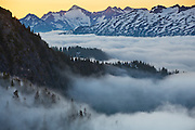 Low clouds fill the valley at sunrise at the base of Damnation Peak in North Cascades National Park, Washington. Primus Peak is visible in the distance.