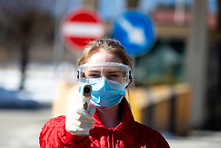 Medic with thermometer gun next to health check point where police officers and medics check travelers at the border crossing with Italy upon entry into Slovenia next to town Ratece, on March 12, 2020 in Ratece, Slovenia. Photo by Matic Klansek Velej / Sportida