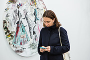 """New York, NY - 5 May 2017. The opening day of the Frieze Art Fair, showcasing modern and contemporary art presented by galleries from around the world, on Randall's Island in New York City. A woman checks her phone in front of a painting by Paulina Ołowska, """"I need to introduce you to each other—you've got so much in common,"""" in the Foksal Gallery Foundation booth."""