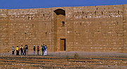 """Tourist observing desert castle """"Qasr al-Kharrana"""" east of Amman. It is a beautiful example of early 8th century Islamic art and architecture. Jordans """"castles"""" actually served various purposes as caravan stations, agriculture and trade centers, resort pavilions and outposts that helped distant rulers forge ties with local bedouins."""