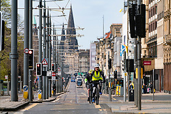 Edinburgh, Scotland, UK. 18 April 2020. Views of empty streets and members of the public outside on another Saturday during the coronavirus lockdown in Edinburgh. Cyclists on a quiet Princes Street. Iain Masterton/Alamy Live News