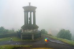 Woman with colourful umbrella and Dugald Stewart monument Calton Hill on foggy , rainy day, Edinburgh, Scotland, UK