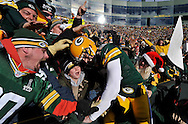 Green Bay Packers quarterback Aaron Rodgers leaps into the crowd as he celebrates his 6-yard touchdown run during the first quarter against the Tennessee Titans at Lambeau Field on December 23, 2012 in Green Bay, Wisconsin.  (UPI)