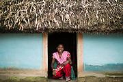Cheerful Manjali Hasda in the doorway of her village home.