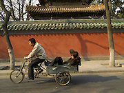 two boys riding a bicycle cart near a temple Beijing China
