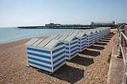 Blue and white beach huts along Hastings seafront on the 20th April 2019 in Hastings in the United Kingdom. Hastings is a town on England's southeast coast, its known for the 1066 Battle of Hastings.