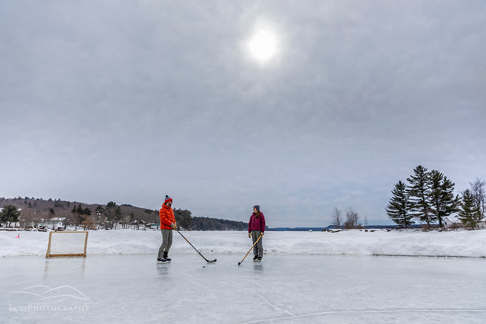 A couple ice skating on Long Lake in Harrison, Maine.