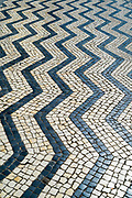 Geometric tiles form shapes and patterns of wavy lines on paving tiles in Aveiro, Portugal