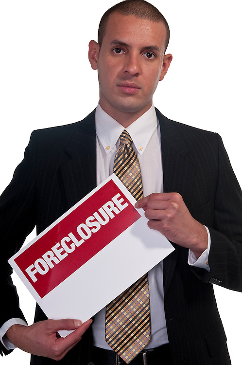 Young man holding a sign of foreclosue and being very worried.