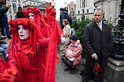 Extinction Rebellion climate change activist performance art troupe the Red Rebel Brigade wearing bright red costumes march silently at Bank in the heart of the City of London financial district on 14th October 2019 in London, England, United Kingdom. Extinction Rebellion is a climate change group started in 2018 and has gained a huge following of people committed to peaceful protests. These protests are highlighting that the government is not doing enough to avoid catastrophic climate change and to demand the government take radical action to save the planet.