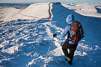 Female hiker walking in snow from Pen Y Fan towards Corn Du, Brecon Beacons national park, Wales